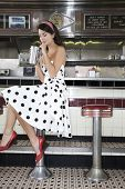 Full length side view of a young woman drinking shake at the diner counter