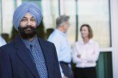 Retrato de un empresario indio confiado con colegas en el fondo