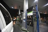 pic of fuel efficiency  - Closeup of cropped car at gas station with view of fuel pumps and natural gas at night - JPG