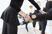stock photo of ballet barre  - Midsection of ballet teacher adjusting foot positions of ballerinas at the barre - JPG