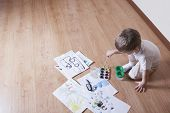 Elevated view of young boy painting with watercolors and paintbrush on laminated floor