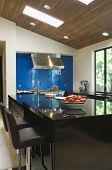 Blue backsplash and breakfast bar in modern kitchen