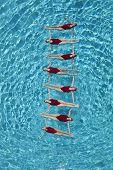 Gruppe von synchronisierte Schwimmer bilden eine Leiter im pool