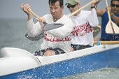 Confident male rower with team paddling outrigger canoe in race