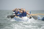 pic of canoe boat man  - Crew of a racing outrigger canoe on water - JPG