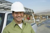 pic of headgear  - Portrait of a smiling construction worker in hardhat standing next to truck on construction site - JPG