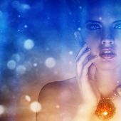 stock photo of mystical  - Portrait of a beautiful girl with a necklace covered in mystic blue and red lights - JPG