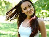 young beautiful lady outdoor portrait, girl with long brown hair posing in  in summer park