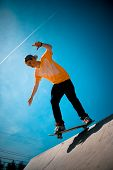 picture of skate board  - A young man skateboarding down a ramp at the skate park - JPG
