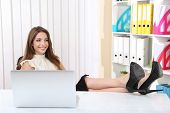 stock photo of table manners  - Businesswoman resting at his office with her shoes on table - JPG