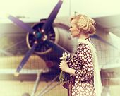 image of propeller plane  - Vintage stylized photo of beautiful girl with a bouquet of daisies and plane on background - JPG