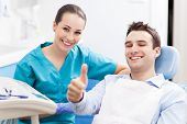 stock photo of thumb  - Man giving thumbs up at dentist office - JPG