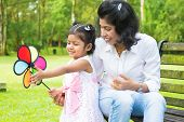 Happy Indian family outdoor activity. Candid portrait of mother and daughter playing windmill at gar