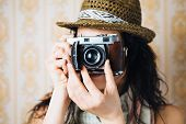 stock photo of  photo  - Hipster woman taking photos with retro film camera on vintage ornamental wallpaper - JPG