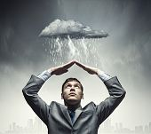Businessman sitting under rain protecting head with arms