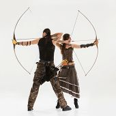 stock photo of longbow  - Young couple has some dangerous hobby - JPG