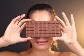 Portrait of beautiful young girl with chocolate on brown background