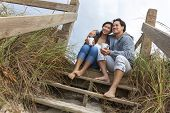 Young Asian Chinese man & woman, boy & girl, couple sitting on wooden steps overlooking a beach drin