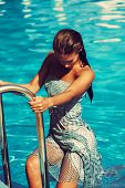 woman get out from the pool wearing blue dress