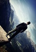 Lonely man standing on the edge of a canyon
