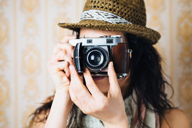image of analogy  - Hipster woman taking photos with retro film camera on vintage ornamental wallpaper - JPG