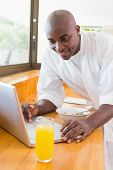 Happy man in bathrobe using laptop at table at home in the kitchen