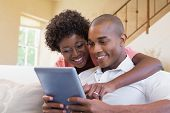 Cute couple relaxing on couch with tablet pc at home in the living room
