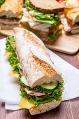 Baguette Sandwich with Mustard, Lettuce,  Fresh Tomatoes, Ham and Cheese