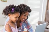 Cute daughter using laptop at desk with mother at home in the living room