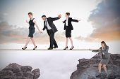 pic of tights  - Young businesswoman pulling a tightrope for business people against rocky landscape - JPG