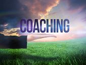 Businesswomans hand presenting the word coaching against green field under orange sky