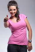 smiling young woman making the ok thumbs up hand gesture in studio