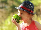 Funny Kid Girl In Hat Eating Big Green Pepper Outdoor Background