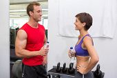 Fit attractive couple chatting holding water bottles at the gym
