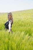 Pretty blonde in sundress standing in wheat field on a sunny day in the countryside