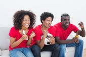 Football fans in red sitting on couch cheering on white background