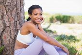 Fit woman sitting against tree smiling on a sunny day in the countryside