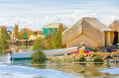 PUNO, PERU, MAY 5, 2014 - Women in traditional attire does her laundry by hand on floating Uros isla