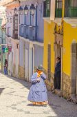 LA PAZ, BOLIVIA, MAY 8, 2014 - Local woman in traditional costume and bowler hat walks down the stre