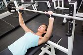 Fit brunette lifting heavy barbell lying on bench at the gym
