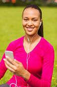 fitness, park, technology and sport concept - smiling african american woman with smartphone and ear