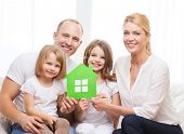 real estate, family, children and home concept - smiling parents and two little girls holding green