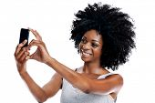 Studio shot of attractive african woman with afro taking a picture of herself with her camera phone