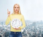 time, education and people concept - serious young woman with wall clock showing 8 and finger up