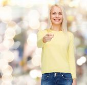 happiness, gesture and people concept - smiling woman pointing finger at you