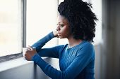 Beautiful african female with afro holding a hot beverage while looking out a window