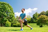fitness, sport, training and lifestyle concept - smiling man stretching leg outdoors