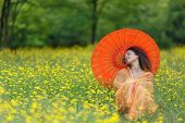 Beautiful elegant woman with an orange parasol draped in a matching chiffon scarf tilting back her h