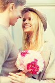 summer holidays, love, relationship and dating concept - happy couple with bouquet of flowers in the