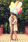 summer holidays, celebration and dating concept - couple with colorful balloons kissing in the park
